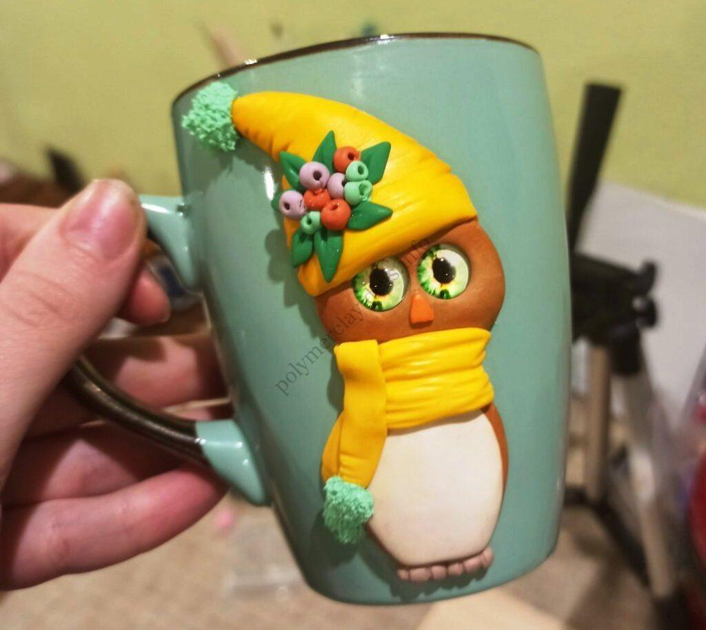 Cute owl made of polymer clay on a cup